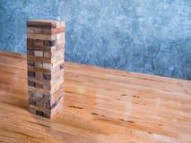 块木比赛或jenga比赛在木桌上与水泥墙壁ba 免版税图库摄影