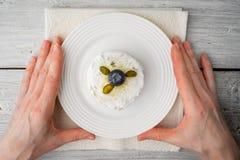结块用开心果和蓝莓在白色板材在手上 免版税图库摄影