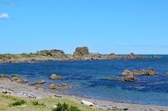 坚固性岩石突出入风平浪静在库克海峡的一个离开的海滩在惠灵顿,新西兰附近 免版税库存图片