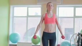 坚定的妇女丢失的重量和行使与哑铃 股票视频