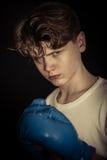 坚定的运动青少年的男孩佩带的拳击手套 免版税库存照片