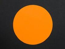 坚实橙色圆盘或圈子反对黑背景 免版税库存图片