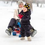 坚强的小男孩运载她的雪撬的母亲 免版税图库摄影