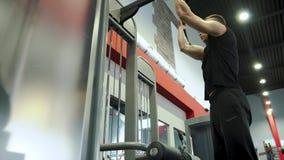 坚强的年轻英俊的男性运动员参与与锻炼机器健身房 股票录像