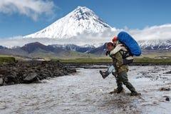 坚强的游人运载她的妇女回到发怒泥泞的山河 图库摄影