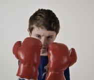 坚强的男孩佩带的拳击手套 库存照片