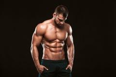 坚强的运动人-显示他完善的后面的健身模型隔绝在与copyspace的黑背景 库存照片