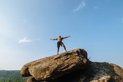 坚强的黑人爱好健美者画象有摆在岩石的赤裸躯干的 蓝色多云天空背景 免版税图库摄影