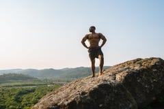 坚强的黑人非裔美国人的人爱好健美者画象有摆在岩石峰顶的赤裸躯干的 蓝色多云天空 免版税库存图片