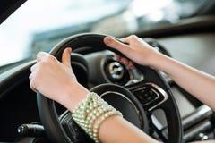 坚持一辆新的汽车的轮子的妇女的手 免版税库存图片