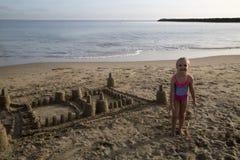 坚持她沙子城堡微笑的逗人喜爱的白肤金发的女孩 库存图片