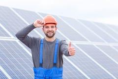 坚持安全帽和显示赞许太阳电池板的关闭upagainst背景工作者 免版税库存照片