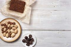 坚果、块菌糖果和巧克力蛋糕在白色背景 免版税图库摄影