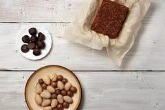 坚果、块菌糖果和巧克力蛋糕在白色背景 库存照片
