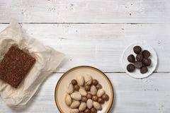 坚果、块菌糖果和巧克力蛋糕在白色背景 免版税库存照片