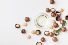 坚果有机马卡达姆坚果油和堆在白色台式视图的 免版税库存照片