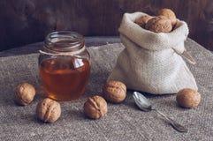 坚果用蜂蜜 在帆布袋子的在瓶子的核桃和蜂蜜 与亚麻布餐巾的木桌 库存照片