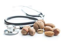 坚果的不同的类型在坚果壳和听诊器的 免版税库存图片