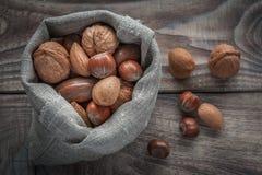 坚果的不同的类型:核桃、榛子、杏仁和胡桃在木桌,选择聚焦上 免版税库存图片