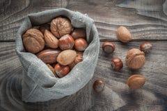 坚果的不同的类型:核桃、榛子、杏仁和胡桃在木桌,选择聚焦上 库存图片