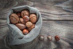 坚果的健康混合:核桃、榛子、杏仁和胡桃在木背景 选择聚焦 免版税库存照片