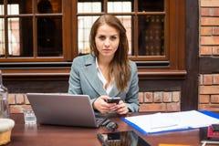 坚硬工作的女实业家在有膝上型计算机和手机的餐馆。 库存照片