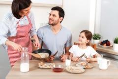 坚硬工作的妻子照片,丈夫和他们的女儿一起坐在厨房用桌上,去吃可口薄煎饼 库存照片
