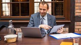 坚硬工作的微笑的商人在有膝上型计算机和垫的餐馆。 图库摄影