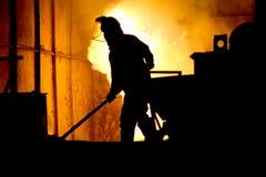 坚苦工作在铸造厂,熔化的铁 免版税库存照片