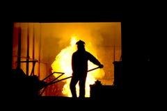 坚苦工作在铸造厂,熔化的铁 图库摄影