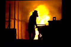 坚苦工作在铸造厂,熔化的铁 免版税库存图片