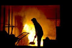 坚苦工作在铸造厂,熔化的铁 库存照片
