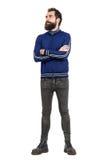 坚韧有胡子的人佩带的田径服夹克和牛仔裤有看横渡的胳膊的  免版税库存照片