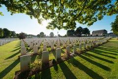 坟墓和树在背后照明,在英国军事公墓在诺曼底, Ranville的 免版税库存照片