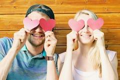 坠入爱河概念-拿着在ey的年轻夫妇纸心脏 免版税库存照片