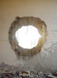 坦克壳在墙壁的冲击孔 免版税库存照片