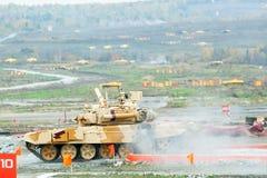 坦克T-90S在水浅滩以后移动 免版税库存图片