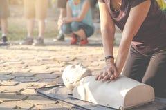 坦率在展示类的CPR的成熟亚洲人女性或更旧的赛跑者妇女训练在室外公园和投入移交CPR 免版税库存照片