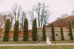 坦率的褂子和毛皮夹克的迷人的年轻新娘在车道秋天停放里面被加强的城堡墙壁 免版税库存照片