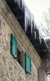 垂悬下来从一个老房子的屋顶的冰柱 免版税库存照片