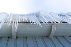 垂悬下来从天沟的冰柱 免版税库存图片