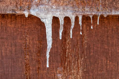 垂悬下来在木墙壁上的冰柱 免版税库存照片