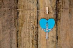 垂悬与在串agains的蓝色心脏的银色金属耶稣受难象 库存图片