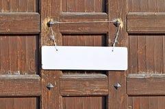 垂悬与在老棕色木墙壁有金属铆钉的-自然织地不很细背景上的被撕碎的绳索的空白的白色标志 免版税库存图片