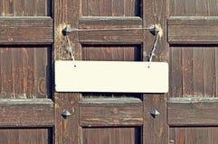 垂悬与在被风化的棕色木墙壁有金属铆钉的-减速火箭的口气背景上的老绳索的空白的白色标志 库存图片