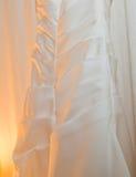 垂悬与软的黄灯的白色婚礼礼服 免版税库存照片