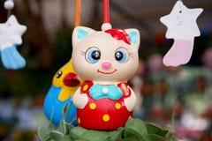 垂悬与陶瓷玩偶backgro的一只五颜六色的陶瓷流动猫 免版税库存图片