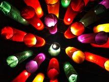 垂悬五颜六色的织品结构的灯在树之间的导线 免版税图库摄影