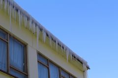 垂悬从一个大大厦的屋顶的冰柱 库存照片