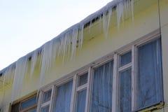 垂悬从一个大大厦的屋顶的冰柱 库存图片